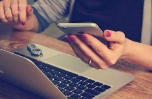 Mulher olhando computador e celular