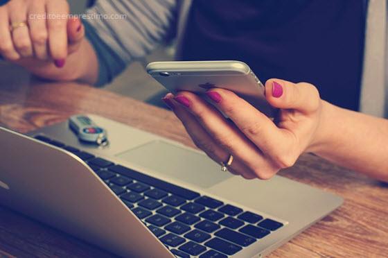 Mulher olhando computador e celular, o que é um título de capitalização