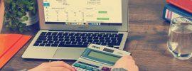 Mulher com calculadora e computador, como fazer crediário nas Lojas CEM