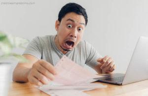 Homem horrorizada olhando boleto com dívidas prescrição